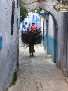 La historia de Chaouen y Vejer. Mujer con leña en calle de Chaouen.